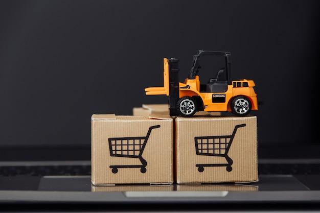Heftruckmodel op kartonnen dozen op een toetsenbord. koeriersdiensten en bezorgingsconcept
