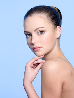 Heide schone huid van jonge mooie vrouw op blauw