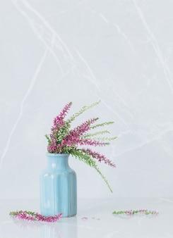 Heideboeket in blauwe vaas op grijze marmeren achtergrond