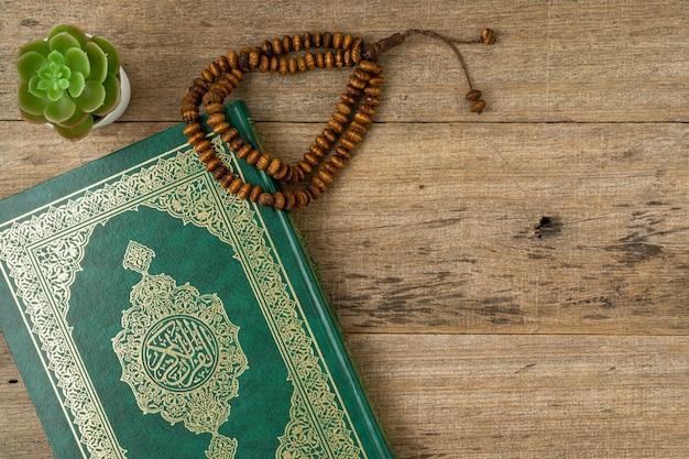 Heilige al quran met geschreven arabische kalligrafie betekenis van al quran en rozenkrans kralen.