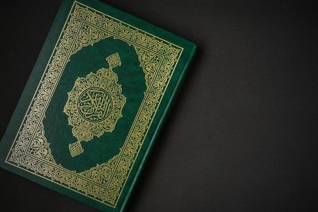 Heilige al quran met geschreven arabische kalligrafie betekenis van al quran op zwarte achtergrond.