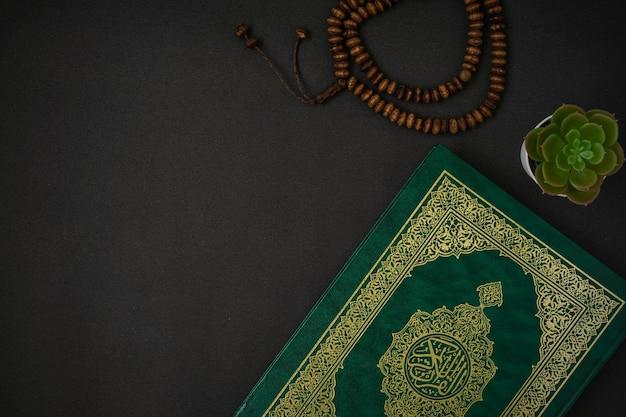 Heilige al quran met schriftelijke arabische kalligrafie betekenis van al quran en rozenkrans kralen op zwart Premium Foto
