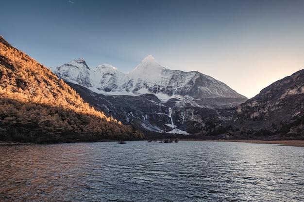 Heilige berg yangmaiyong op rivier in de herfstvallei bij avond