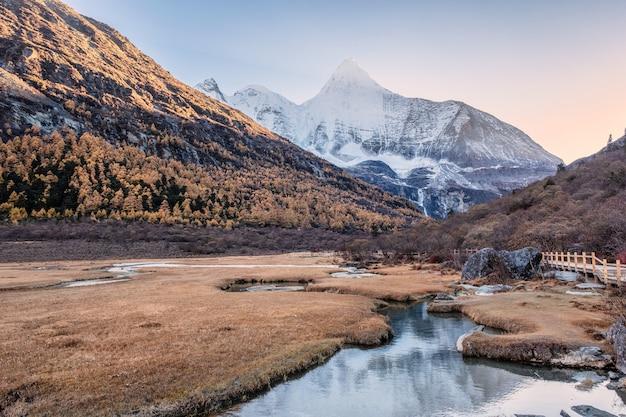Heilige berg yangmaiyong reflectie op rivier in herfst vallei
