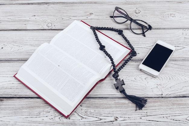 Heilige bijbel en smartphone met zwarte koffiekop op hout.