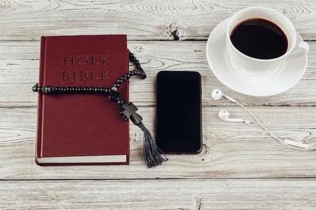 Heilige bijbel en smartphone met zwarte koffiekopje