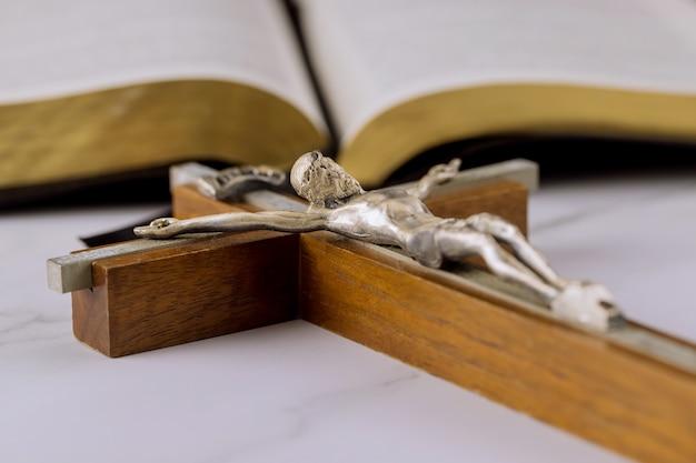 Heilige bijbel op de achtergrond van het christelijke kruis de hoop van de mensheid op redding op weg naar god door gebed.