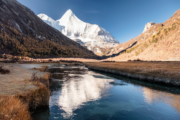 Heilige sneeuw berg yangmaiyong reflectie op de rivier in de herfst vallei op het plateau