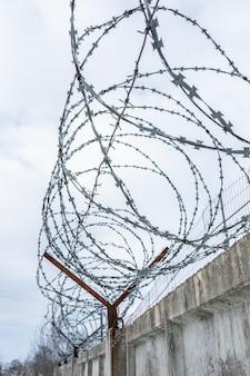 Hek met metalen prikkeldraad weer bewolkte hemel. beschermd gebied, bewaakt object, gevangenis.