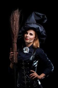 Heks in een zwarte hoed met een bezem