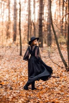 Heks in het herfstbos. een meisje in een zwarte lange jurk loopt in het bos.