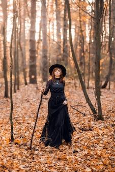 Heks in het herfstbos. een vrouw in een zwarte lange jurk met een wandelstok.