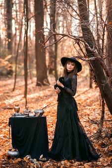 Heks in het herfstbos. een vrouw met een zwarte kat bereidt zich voor op halloween.