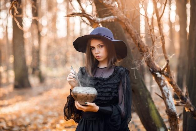Heks in het herfstbos. portret van een meisje in een zwarte jurk met een drankje.