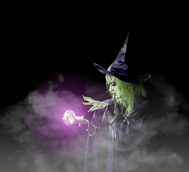 Heks in het zwart spelt donkere magie met marmer.