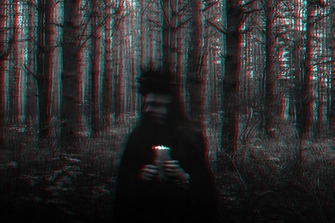 heks in kostuum voert donkere spreuken uit met kaarsen in het bos. wazige foto met vervaging door lange belichtingstijd. zwart-wit met 3d glitch virtual reality-effect