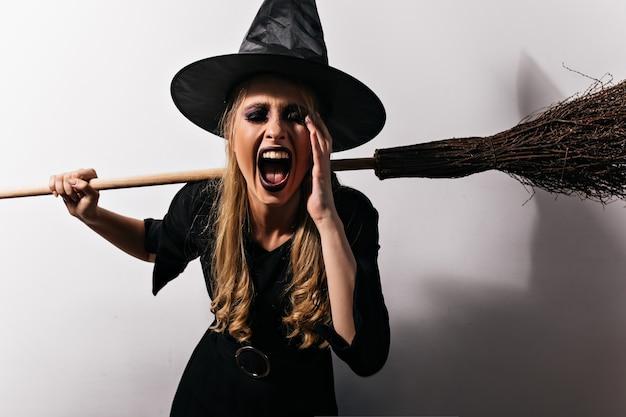 Heks met lang blond haar die op witte muur gillen. jonge vrouwelijke tovenaar die haar magische bezem houdt.