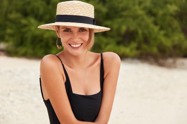 Helder beeld van de vrouw ziet er gelukkig uit en toont haar perfecte slanke lichaam, draagt bikini en hoed, baadt overdag in de zon in de zomer, ontspant buiten in tropisch strand