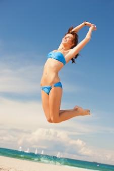 Helder beeld van gelukkig springende vrouw op het strand.