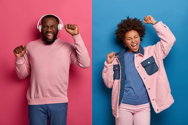 Helder beeld van gelukkige vrouw en man dansen zorgeloos, handen opsteken, bewegen met het ritme van muziek, bebaarde zwarte man draagt een koptelefoon, lacht positief, luistert naar favoriete muziek. levensstijl en plezier