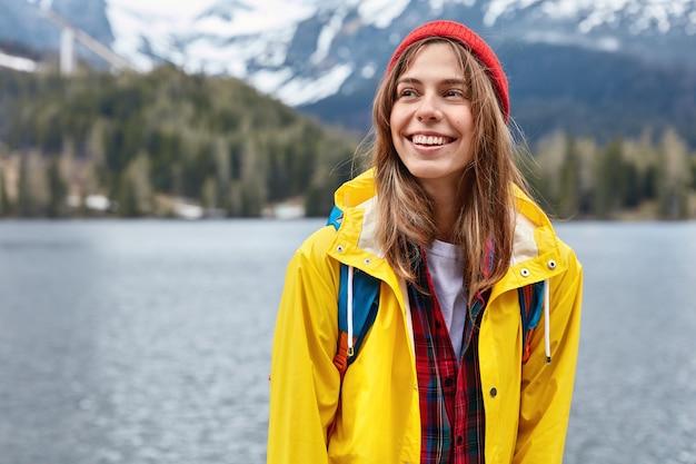 Helder beeld van jonge vrouwelijke reiziger staat tegen bergmeer ruimte, draagt stijlvolle rode hoed en gele jas