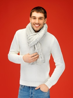 Helder beeld van knappe man in warme trui en sjaal.