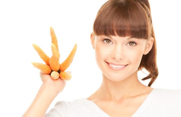 Helder beeld van mooie huisvrouw met wortelen over wit