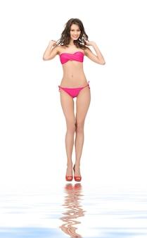 Helder beeld van mooie vrouw in bikini en hoge hakken