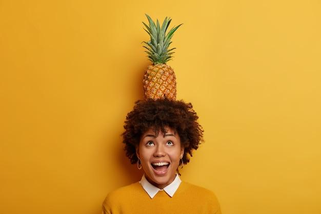 Helder beeld van opgetogen speelse ondeugende afro-amerikaanse vrouw houdt ananas op het hoofd lacht en kijkt positief boven draagt levendige gele trui geniet van het eten van zomervoedsel. goed gezind