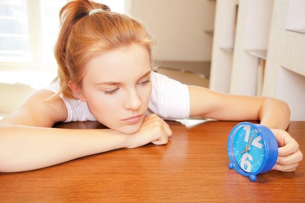 Helder beeld van peinzend tienermeisje met klok