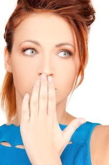 Helder beeld van tienermeisje met hand over mond