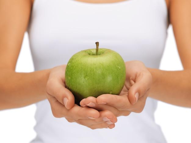 Helder beeld van vrouwelijke handen met groene appel