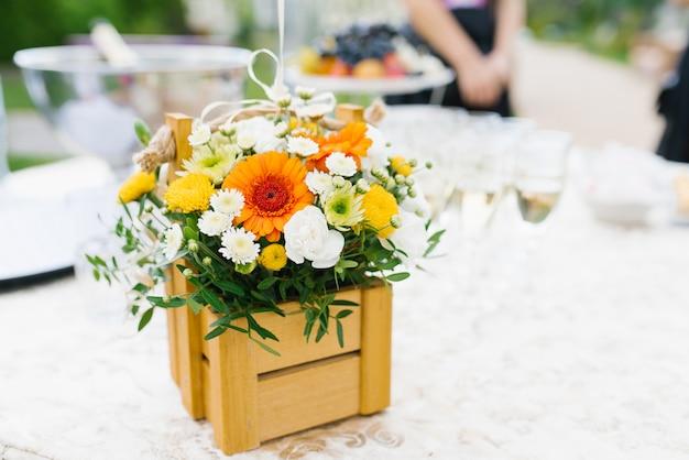 Helder bloemstuk van witte, gele en oranje chrysantenbloemen in een houten doos