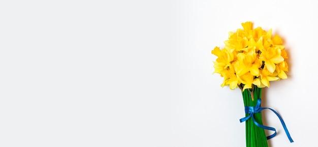 Helder boeket, geurige lentebloemen, narcissen op een blauwe achtergrond met ruimte voor tekst