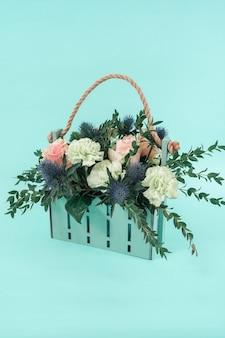 Helder boeket in een designmand in mintkleur. stijlvolle bloemen voor het decor van een evenement.