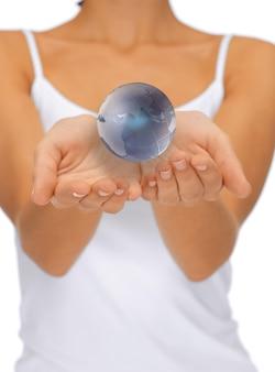 Helder close-upbeeld van vrouwenhanden die aardebol houden