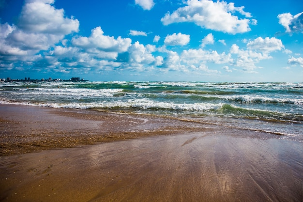 Helder en kleurrijk zeegezicht aan zee blauwgroene golven en blauwe lucht met wolken ruimte kopiëren
