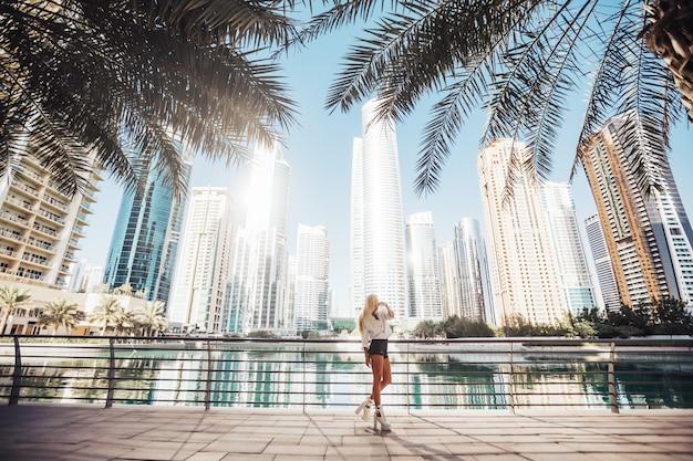 Helder en schoon met uitzicht op het meer in een stedelijke stad, emiraten, golfland, levensstijl. russische dame fotografie in de stad met een hoog gebouw in de omgeving.