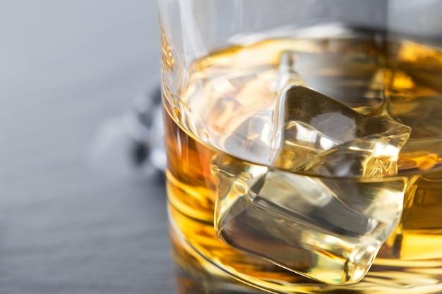 Helder fragment van whisky met ijs in een glas