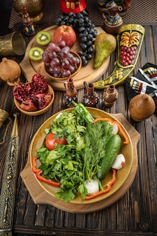 Helder frisse groene salade bladeren met rode tomaten, komkommers en radijs in de witte kom op houten achtergrond. hoge kwaliteit foto