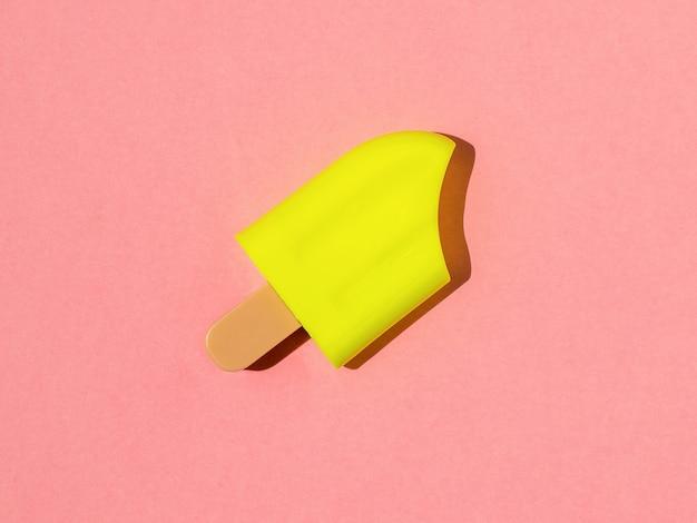 Helder geel ijs in fel licht op een roze achtergrond.