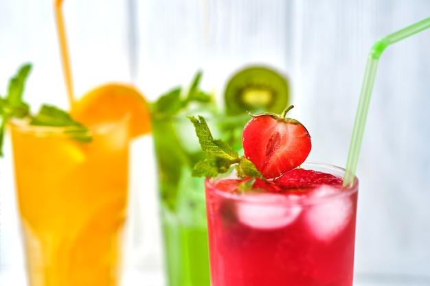 Helder gekleurde heerlijke koude limonade van aardbei en sinaasappel en kiwi met munt op lichte ondergrond