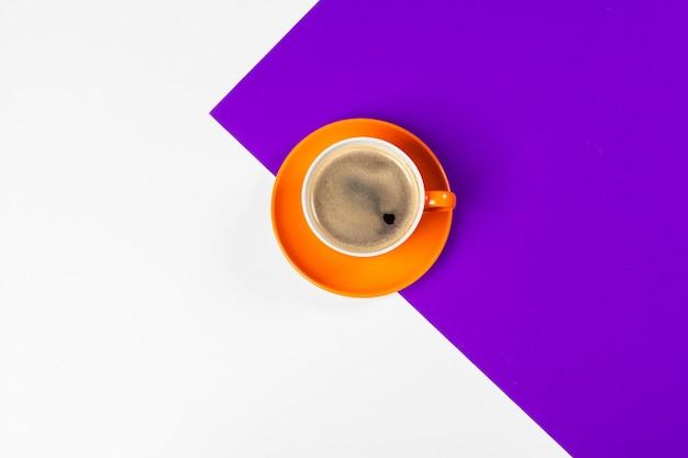 Helder gekleurde koffiekopje op een tafelblad bekijken