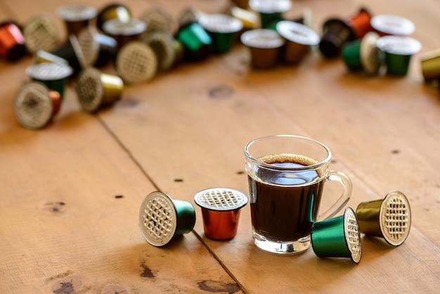 Helder glazen koffiekopje omgeven door gebruikte koffiepads op houten tafel.