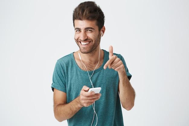 Helder glimlachend ongeschoren spaanse man in blauw t-shirt, met smartphone, muziek luisteren met een koptelefoon, lachen en gebarend. positieve menselijke gezichtsuitdrukkingen en emoties
