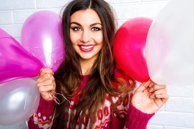 Helder grappig levensstijlbeeld aan mooie jonge vrouw in ongedwongen trendy sweater die pret hebben en partijballons houden.