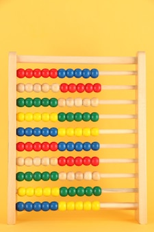 Helder houten stuk speelgoed telraam, op gele achtergrond