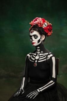 Helder. jong meisje zoals santa muerte saint dood of suikerschedel met lichte make-up. portret geïsoleerd op donkere groene studio achtergrond met copyspace. het vieren van halloween of dag van de doden.