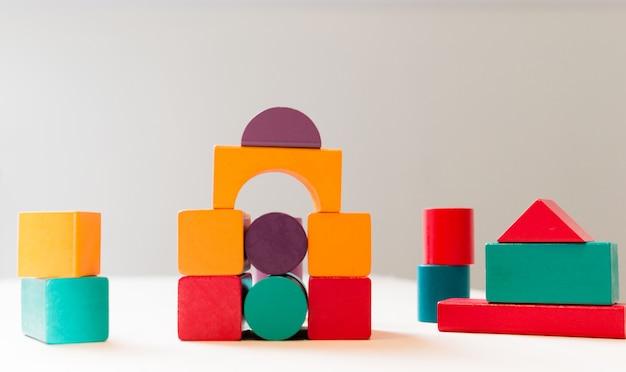 Helder kleurrijk houten blokkenstuk speelgoed. bakstenen kinderen toren bouwen, kasteel, huis.
