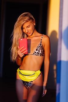 Helder kleurrijk stijlvol portret van jonge fit slanke blogger vrouw in luipaard bikini bij warm zonsonderganglicht foto nemen